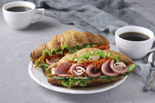 Two croissants-sandwiches with lettuce, carrots, cucumbers, sausage, cheese and two cups of coffee on a light grey concrete background. Breakfast or lunch concept. Closeup
